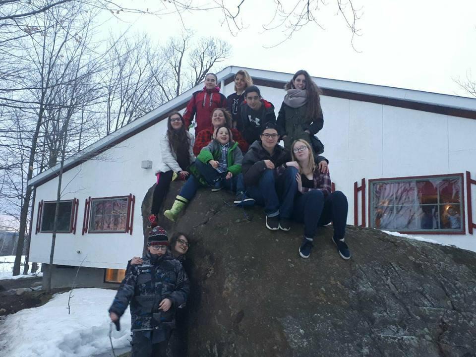 Groupe assis sur une roche à la cabane à sucre