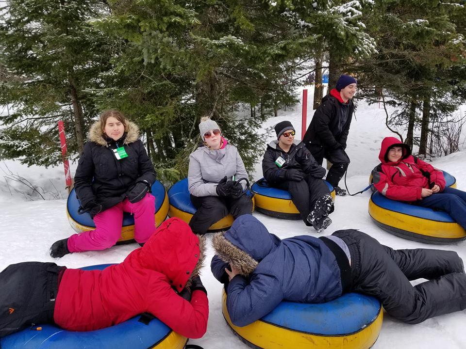 Groupe de jeunes se repose sur les tubes de glissades en hiver