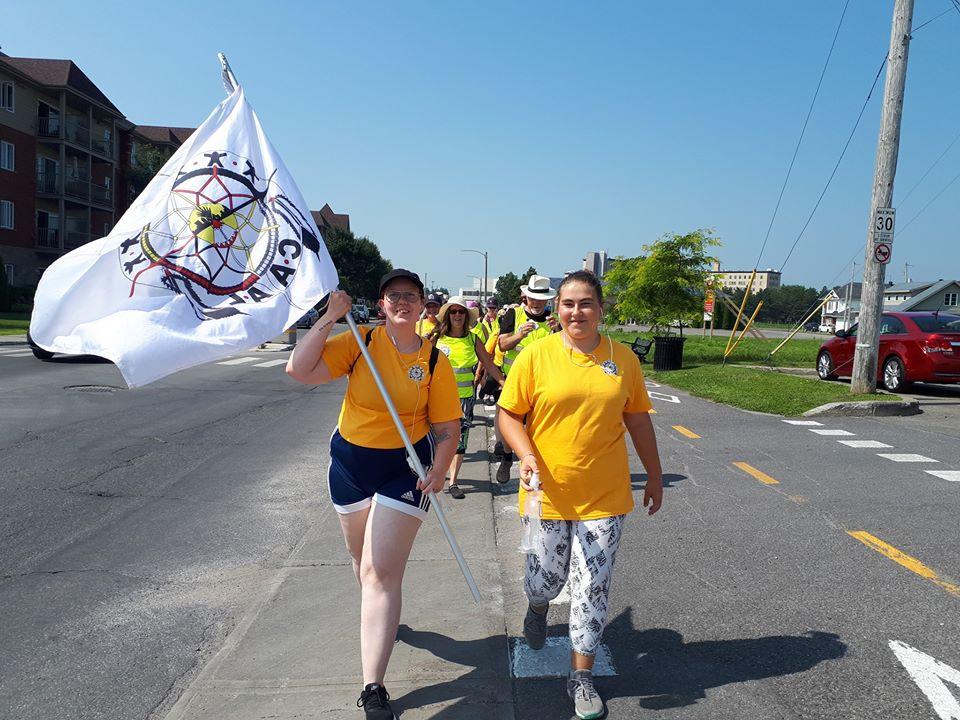Deux jeunes porte le drapeau du CAAL en marchant